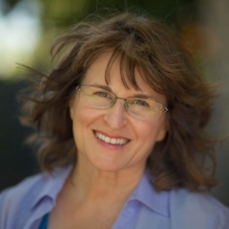 Photo of Karla McLaren, a smiling middle-aged caucasian woman with wavy brown hair, green eyes, and glasses.